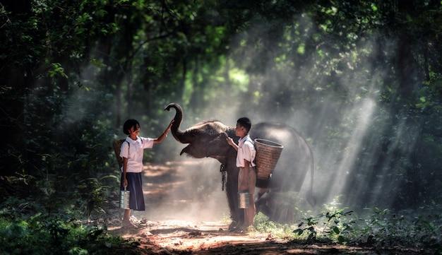 Kleiner asiatischer junge des studenten und mädchen, landschaft in thailand