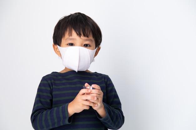 Kleiner asiatischer junge mit gesundheitsmaske schützen virus auf weiß