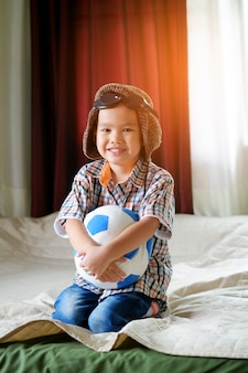 Kleiner asiatischer junge spielt mit ball, reise-und abenteuer-konzept
