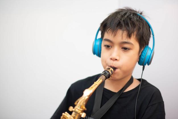 Kleiner asiatischer junge studiert saxophoninstrumentmusik online zu hause