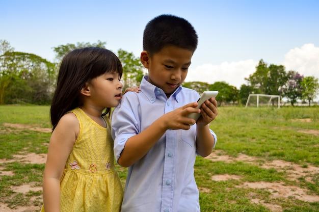 Kleiner asiatischer junge und mädchen benutzen das intelligente telefon / die tablette für das spielen des spiels.