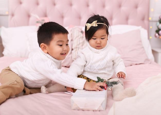 Kleiner asiatischer kinderjunge und eine frau in pullovern öffnen geschenke und spielen, während sie zu hause auf dem bett sitzen