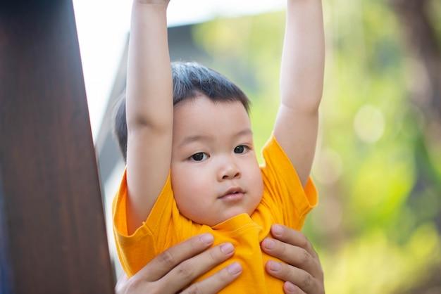 Kleiner asiatischer kleinkindjunge, der auf dem seil am spielplatz klettert