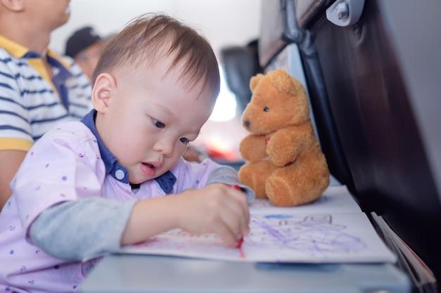 Kleiner asiatischer kleinkindjunge, der während des fluges im flugzeug ein malbuch mit buntstiften ausmalt