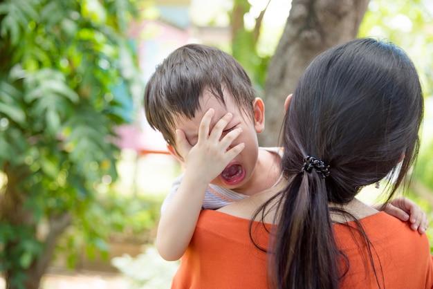 Kleiner asiatischer schreiender junge während mutter, die ihn hält, um zur schule zu gehen
