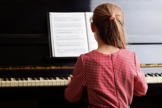 Kleiner begabter mädchenmusiker, der das klavier spielt