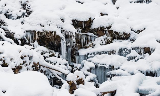 Kleiner bergwasserfall aus eisigem wasser fließt zwischen nassen steinen, die mit weißem schnee bedeckt sind