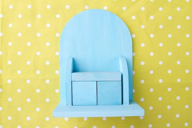 Kleiner blauer minischrank auf einer gepunkteten gelben hintergrundspielzeugmöbel-draufsicht
