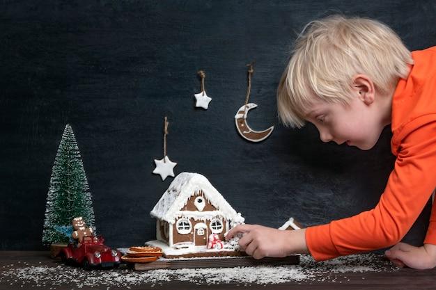 Kleiner blonder junge berührt weihnachtskomposition aus lebkuchenhaus, spielzeugauto und weihnachtsbaum.