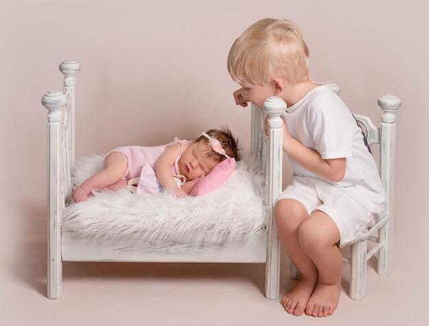 Kleiner blonder junge, der auf schlafendes baby schaut