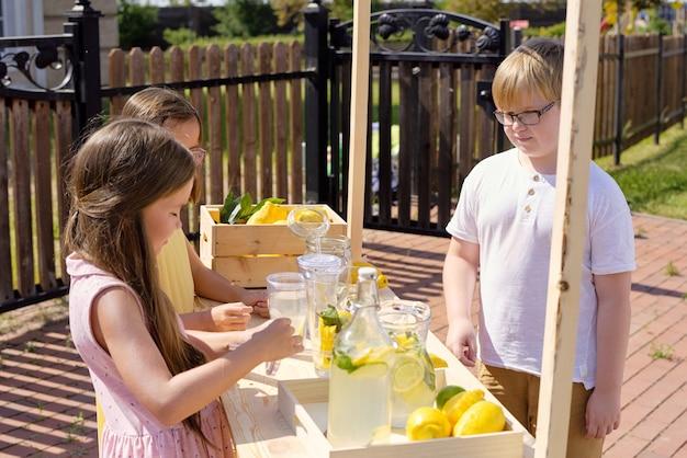 Kleiner blonder junge, der durch hölzernen stall steht und glas der frischen hausgemachten limonade kauft, die von zwei entzückenden mädchen gebildet wird