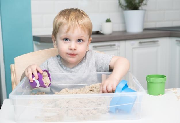 Kleiner blonder junge, der mit kinetischem sand zu hause spielt.