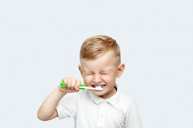 Kleiner blonder junge, der seine zähne im inländischen bad putzend lernt