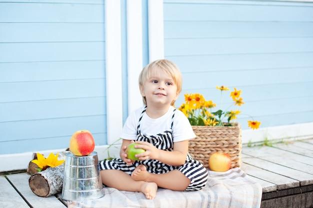 Kleiner blonder junge, der zu hause auf einer hölzernen veranda sitzt und an einem herbsttag einen apfel isst. kindheitskonzept. im herbst spielt ein kind auf dem hof. glückliches baby. ernte. kleiner bauer. obst und baby