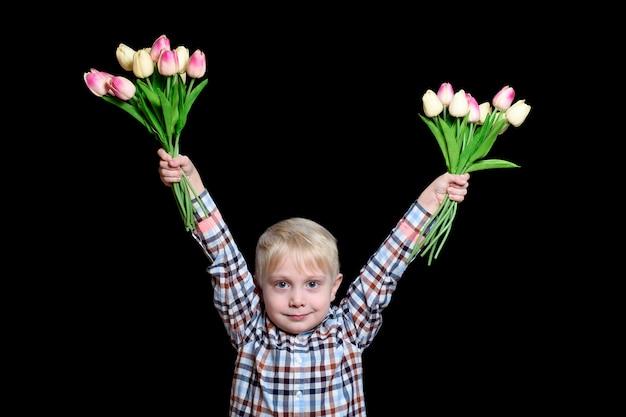 Kleiner blonder junge, der zwei blumensträuße von tulpen hält. porträt.