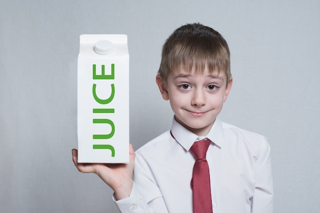 Kleiner blonder junge hält und zeigt ein großes weißes kartonsaftpaket. weißes hemd und rote krawatte. heller hintergrund.