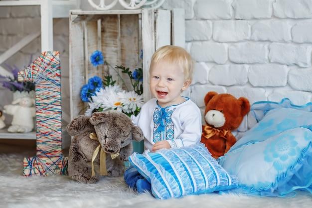 Kleiner blonder junge im traditionellen ukrainischen bestickten hemd, das mit spielzeugen im studio spielt, verziert