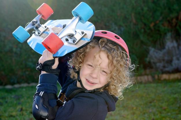 Kleiner blonder junge mit skateboard