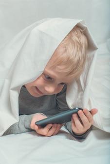 Kleiner blonder junge passt etwas auf einem smartphone auf. im bett liegen und sich unter der decke verstecken. gadget freizeit