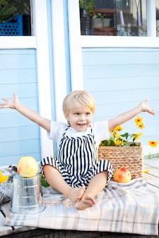 Kleiner blonder junge sitzt auf einer hölzernen veranda zu hause mit vergnügen an einem herbsttag. kindheitskonzept. im herbst spielt ein kind auf dem hof. glückliches kind. ernte. kleiner bauer. sich um ein baby kümmern.