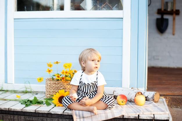 Kleiner blonder junge sitzt zu hause auf einer holzveranda glückliches kind spielt im sommerhof