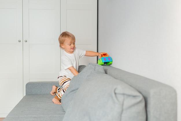 Kleiner blonder junge spielt mit einem spielzeugauto auf einem grauen sofa