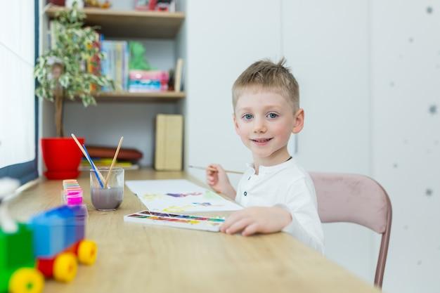 Kleiner blonder junge zeichnet in seinem zimmer, sitzt an einem tisch und hat spaß