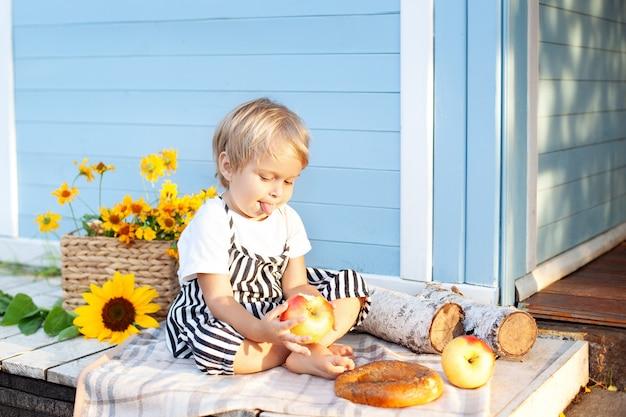Kleiner blonder junge zeigt zunge, die an einem herbsttag auf einer hölzernen veranda zu hause sitzt. kindheitskonzept. ein kind spielt im hof eines landhauses. das baby ist glücklich. kinderfrühstück. ernte