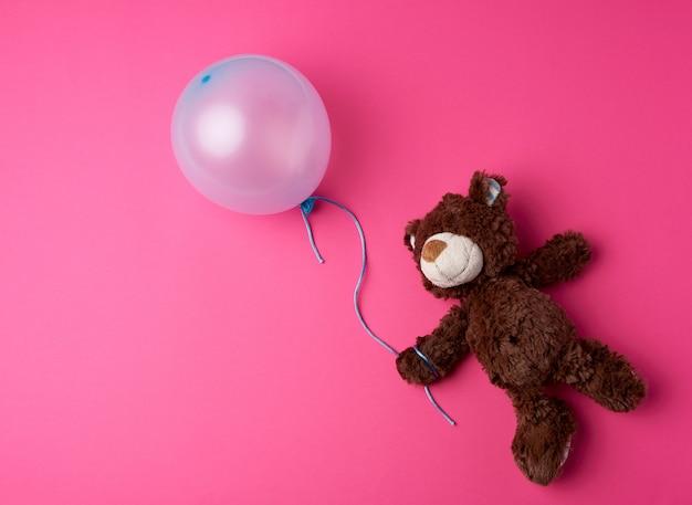 Kleiner brauner teddybär, der einen blauen aufgeblasenen ballon hält