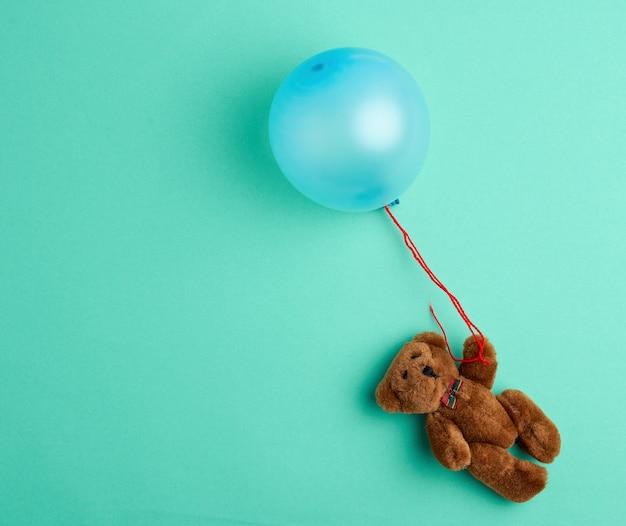 Kleiner brauner teddybär, der einen rosa aufgeblasenen ballon hält