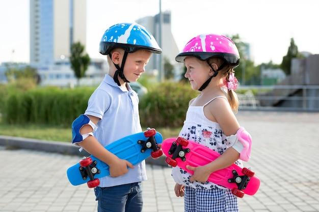 Kleiner bruder und kleine schwester gehen im sommer im park skateboard fahren, sie schlagen ihre helme auf und lächeln