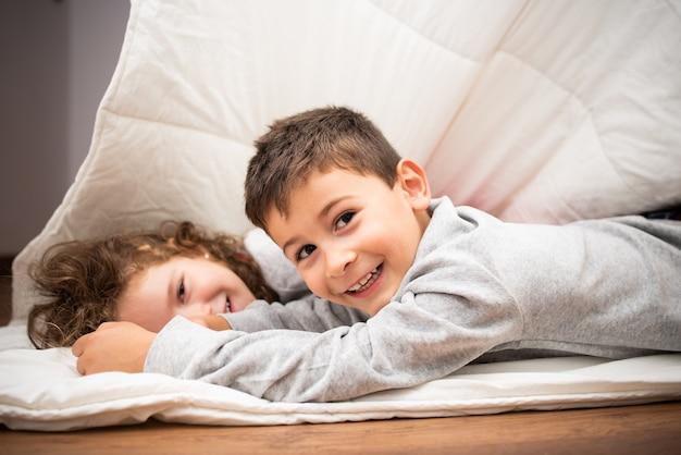Kleiner bruder und schwester spielen zusammen im schlafzimmer