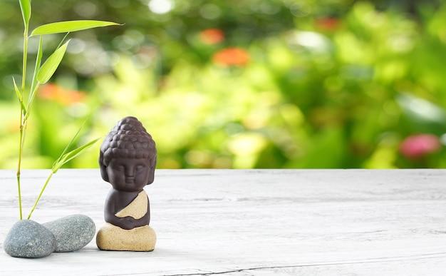 Kleiner buddha meditiert auf holztisch und verschwimmt