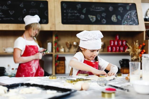 Kleiner chef charmantes mädchen macht spaß, kekse aus einem teig in einer gemütlichen küche zu machen