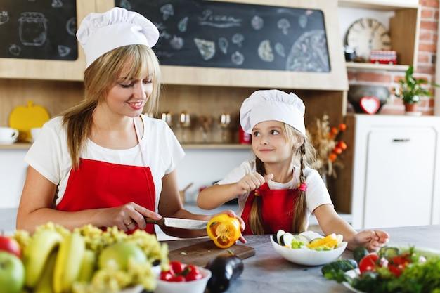 Kleiner chef mutter und charmante tochter bereiten gemüse in einer gemütlichen küche zu