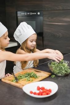 Kleiner chef zwei, der lebensmittel in der küche zubereitet