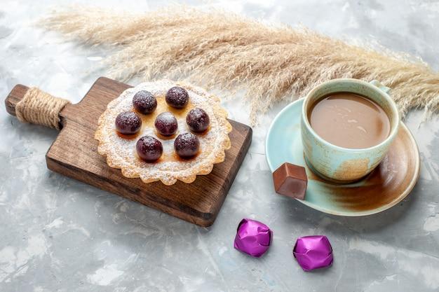 Kleiner chery kuchen mit milchkaffee auf weißem schreibtisch, süßes zuckerfruchtgetränkfoto