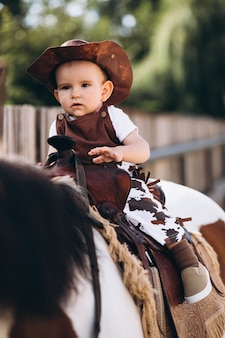 Kleiner cowboy, der auf einem pferd sitzt