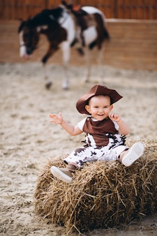 Kleiner cowboy, der auf heu sitzt