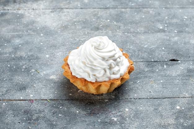 Kleiner cremiger kuchen gebacken köstlich isoliert auf grauer, süßer zuckercreme des kuchenkekses