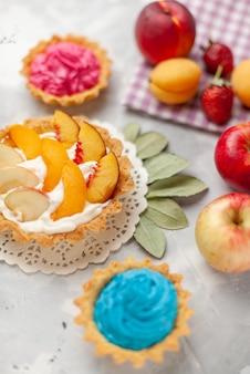 Kleiner cremiger kuchen mit geschnittenen früchten und weißer sahne zusammen mit cremigen kuchen und früchten auf hellem schreibtisch, obstkuchen-kekskeks süß