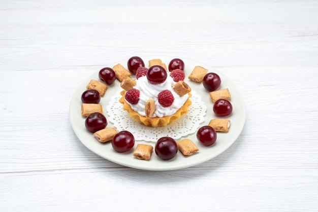 Kleiner cremiger kuchen mit himbeeren und kleinen keksen auf weißlicht