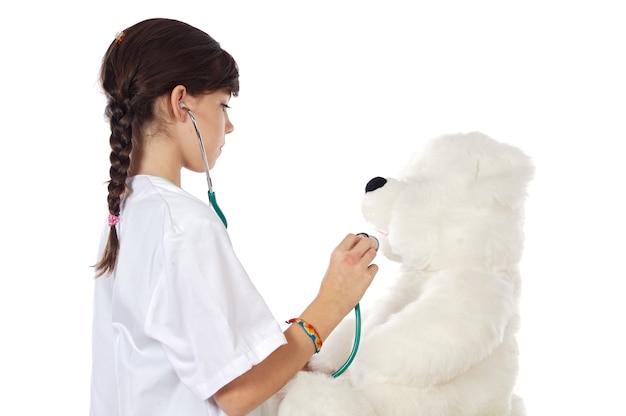 Kleiner doktor, der ihren bären a über weißem hintergrund überprüft