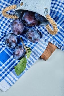 Kleiner eimer gartenpflaumen auf blauer tischdecke.