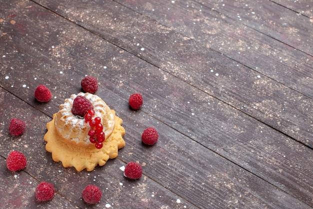 Kleiner einfacher kuchen mit zuckerpulver himbeere und preiselbeeren auf braunem rustikalem schreibtisch, beerenfruchtkuchen süßer auflauf
