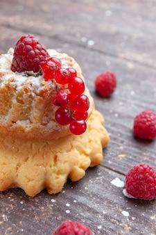Kleiner einfacher kuchen mit zuckerpulver himbeere und preiselbeeren auf rustikalem schreibtisch
