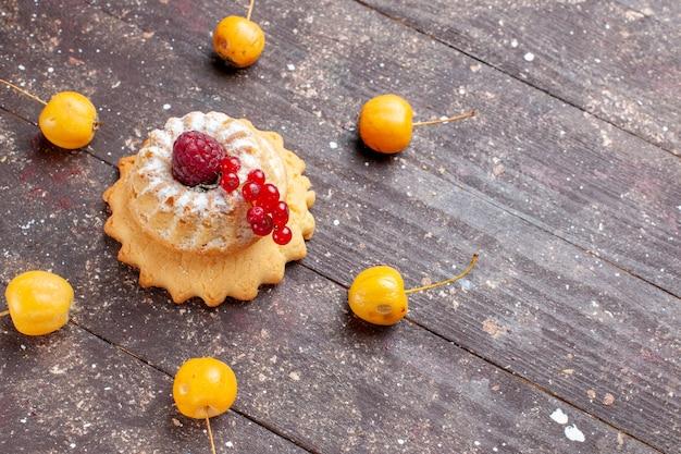 Kleiner einfacher kuchen mit zuckerpulver himbeere und preiselbeeren gelbe kirschen auf braunem holz rustikal, beerenfruchtkuchen süß backen