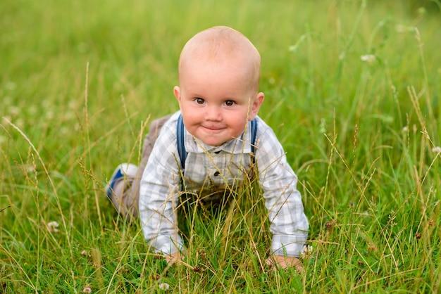 Kleiner einjähriger junge im grünen gras.