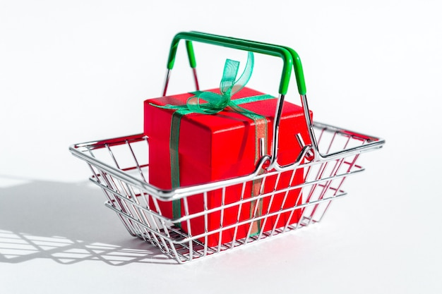Kleiner einkaufskorb mit roter geschenkbox auf weiß
