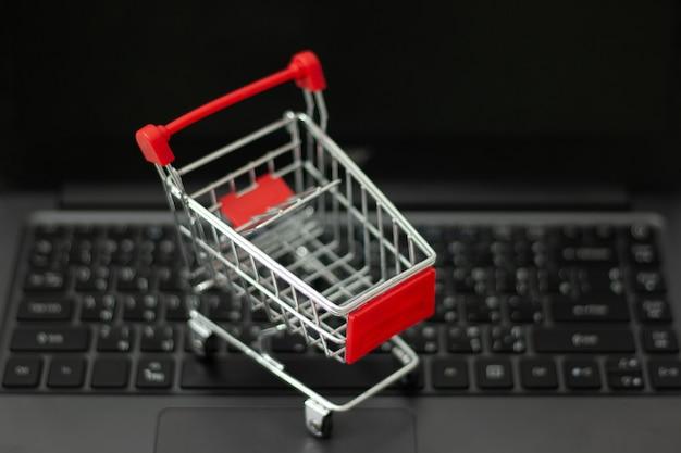 Kleiner einkaufswagen auf dem laptop für online-shopping. online-shopping-konzept.